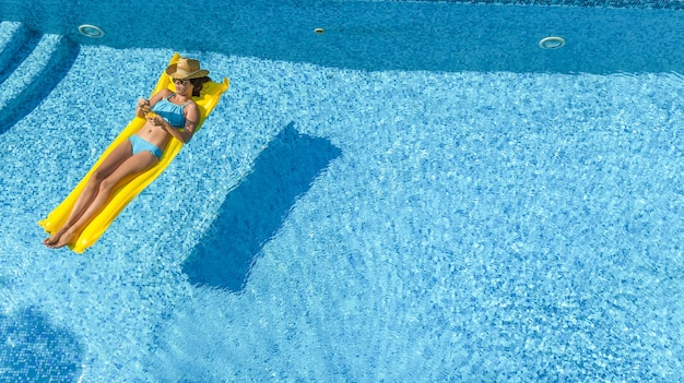 팽창 식 매트리스 공중보기에 수영장 여자에서 편안한 아름 다운 젊은 여자