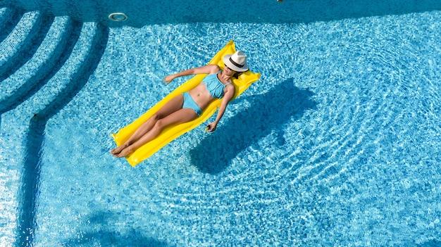 수영장에서 편안한 아름 다운 어린 소녀, 풍선 매트리스에 여자, 공중보기