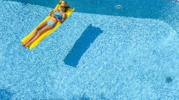 Beautiful young girl relaxing in swimming pool woman on inflatable mattress aerial view