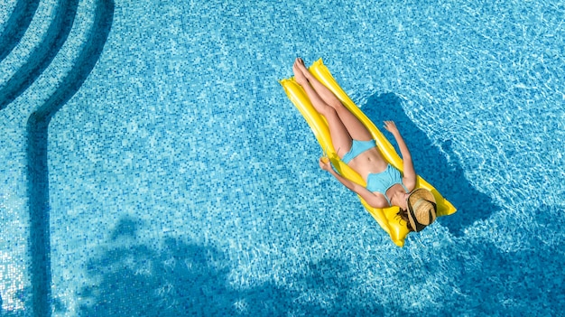 Beautiful young girl relaxing in swimming pool, woman on inflatable mattress, aerial view