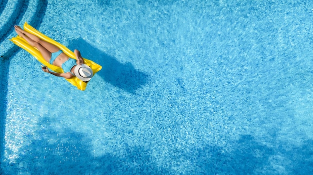 Beautiful young girl relaxing in swimming pool, woman swims on inflatable mattress and has fun in water on family vacation, tropical holiday resort, aerial drone view from above