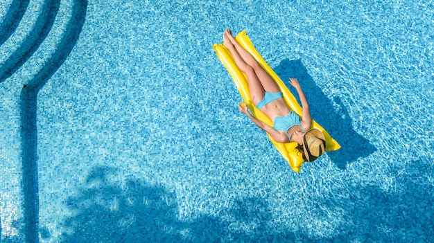 Beautiful young girl relaxing in swimming pool, woman swims on inflatable mattress and has fun
