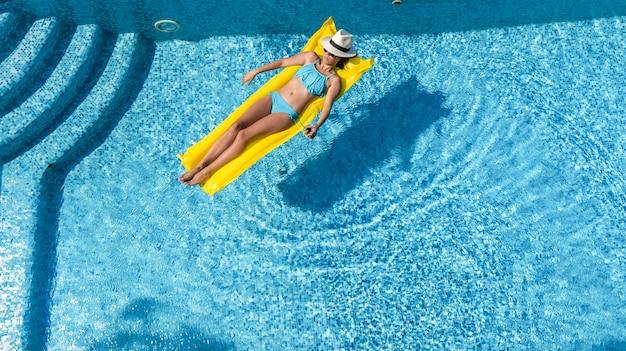 Beautiful young girl relaxing in swimming pool