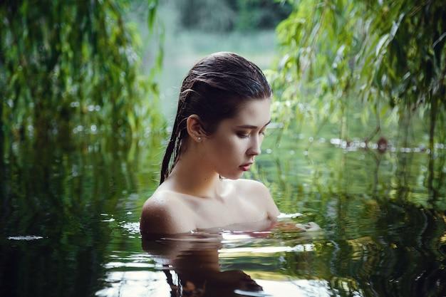 水で休んでいる美しい少女。女性は盲目的に、川に浮かび、水中で瞑想します
