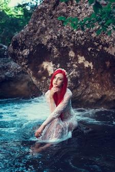 水で休んでいる美しい少女。白いドレスを着た若い女性が小川の真ん中にある石の上に座っています。