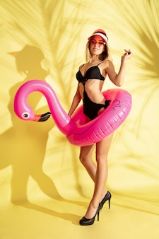 팜 그림자와 노란색 스튜디오 배경에 고립 된 아름 다운 젊은 여자의 전체 길이 초상화. 유행 bodysuit에서 포즈를 취하는 여자. 표정, 여름, 주말 개념. 트렌디 한 색상.