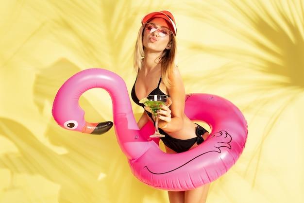 팜 그림자와 노란색 스튜디오 벽에 고립 된 아름 다운 젊은 여자의 절반 길이 초상화. 유행 bodysuit에서 포즈를 취하는 여자. 표정, 여름, 주말 개념. 트렌디 한 색상.