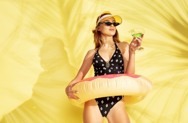 Beautiful young girl's half-length portrait isolated on yellow studio background with the palm shadows. woman posing in fashionable bodysuit. facial expression, summer, weekend concept. trendy colors.