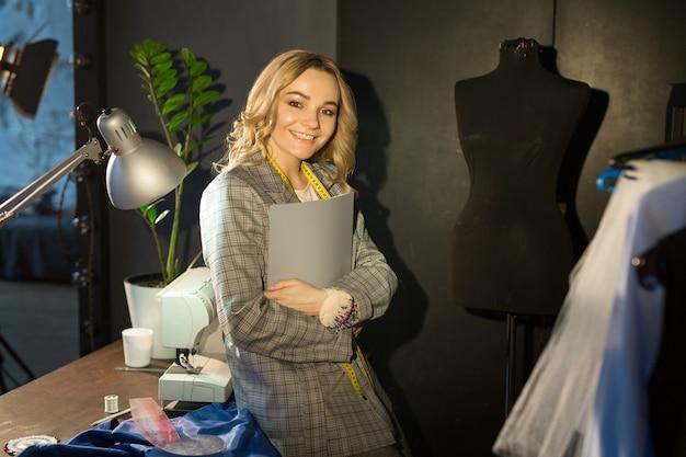 Красивая молодая девушка шьет платье на швейной машинке ночью на работе