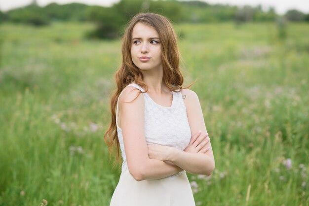 Красивая молодая девушка показывает недовольство в природе