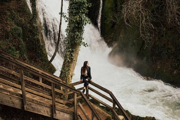 Beautiful young girl siting near amazing waterfall in terni, italy.