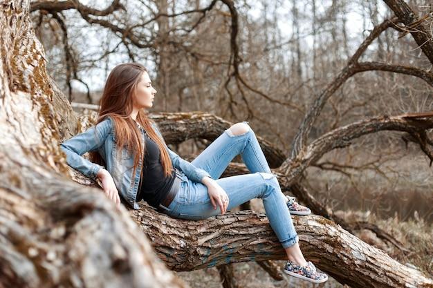 Красивая молодая девушка сидит и мечтает на ветке дерева