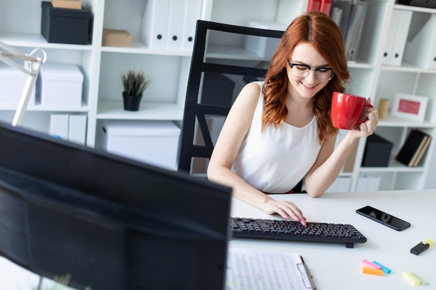 Beautiful young girl sits at the desk in the office, holds a cup in one hand and works at the computer.