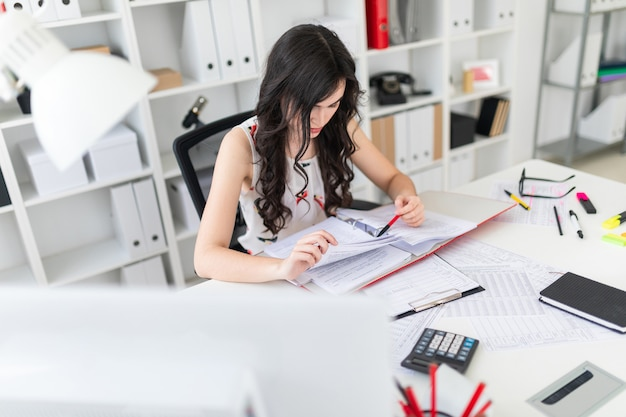 A beautiful young girl sits at an office desk is holding a pen in her hand and thumbs through a folder with documents.