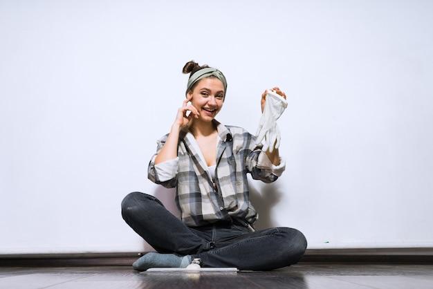 Красивая молодая девушка сидит на полу, делает ремонт в своей новой квартире, сняла резиновые перчатки