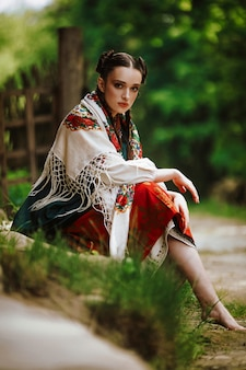 Beautiful young girl sits in a park in a colorful ukrainian dress