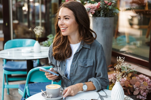 Beautiful young girl sitting at the cafe outdoors, drinking coffee