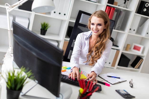 Beautiful young girl sitting at desk in office and working at computer. before the girl there are documents.