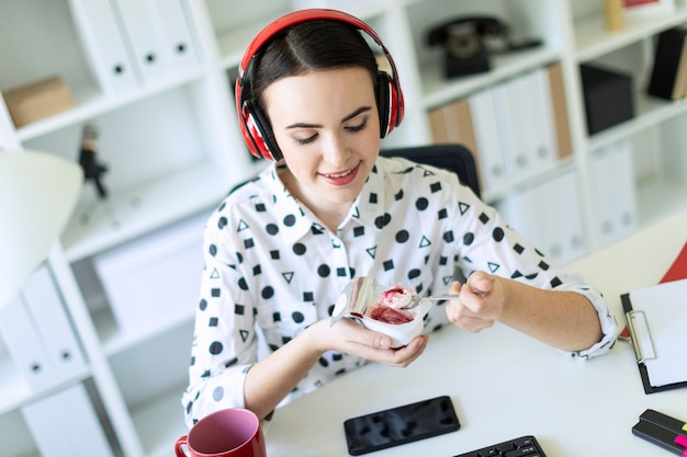 Beautiful young girl sitting in headphones at desk in office eating yogurt with red filling.