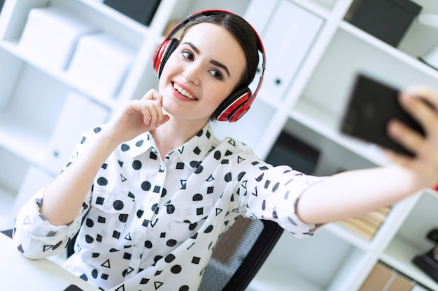 Beautiful young girl sitting in headphones at desk in office and taking pictures of herself on the phone.