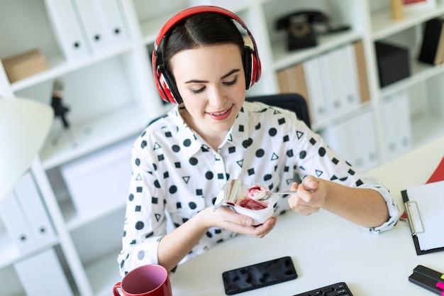 赤い詰物とヨーグルトを食べるオフィスの机でヘッドフォンに座っている美しい少女。