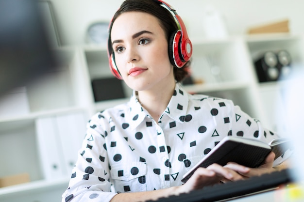 オフィスのデスクでヘッドフォンに座っている美しい少女