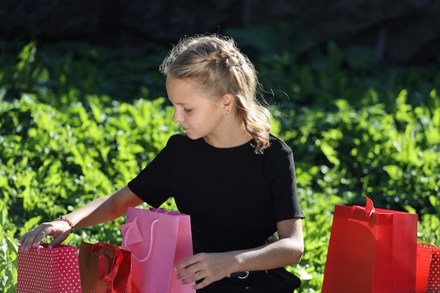 色付きのバッグと公園に座っている美しい少女