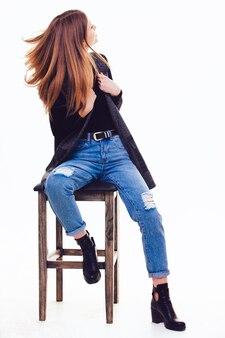 スタジオの椅子に座っている美しい少女。絶縁付き。