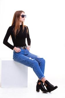 Красивая молодая девушка, сидя на белом кубе в студии с изоляцией.