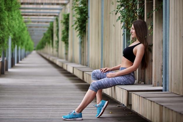 Красивая молодая девушка сидит на деревянной скамейке после тренировки