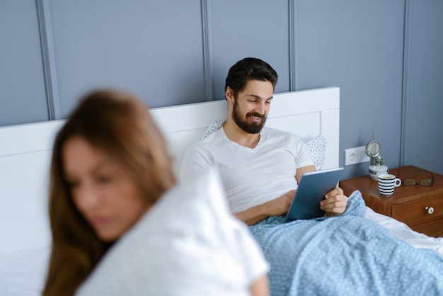 Красивая молодая девушка сидит на кровати и грустит, пока ее парни не обращают на нее внимания. он улыбается и смотрит на свой планшет.