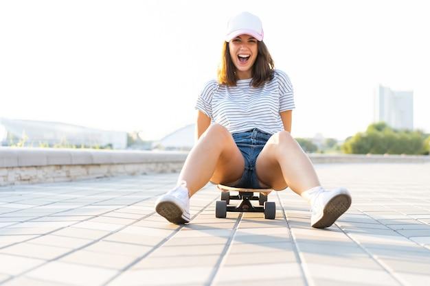 화창한 날씨에 longboard에 앉아 아름 다운 젊은 여자.
