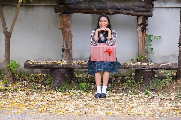 ギフトボックスと木の下に座っている美しい少女。