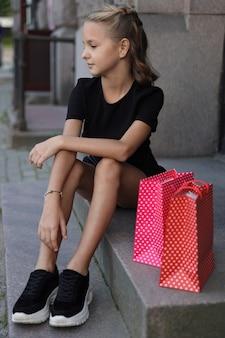 店の階段に色付きのバッグと座っている美しい少女