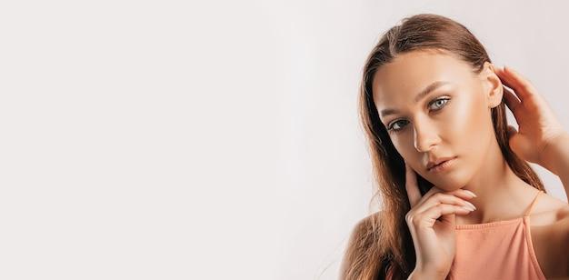 아름 다운 어린 소녀 웃 고 흉내와 흰색 고립 된 배경에 카메라를 찾고 포즈. 긍정적인 갈색 머리 여자입니다. 친절한 모습. 뷰티페이스
