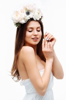 美しい少女の笑顔と白いドレスの肖像画の白い壁に花でポーズ
