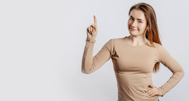 Beautiful young girl smiling and pointing her finger to the side at on white isolated background. a woman points to an idea, a place for advertising. positive brunette in a beige jumper.