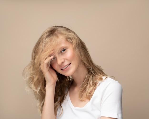 Красивая молодая девушка улыбается. симпатичная блондинка с вьющимися волосами в белой футболке на бежевой стене