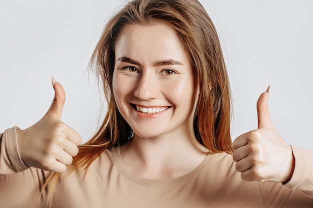 Beautiful young girl smiling and shows thumbs up gesture with two hands on a white isolated background.