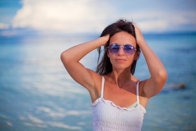 Красивая молодая девушка, стоя на пляже