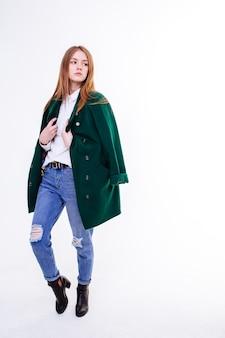 Красивая молодая девушка стоя в пальто. студийная изоляция.