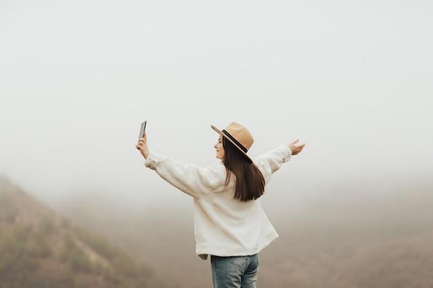 언덕에 서 있고 스마트 폰에 selfie를 만드는 아름 다운 젊은 여자. 배경에 안개 언덕입니다.