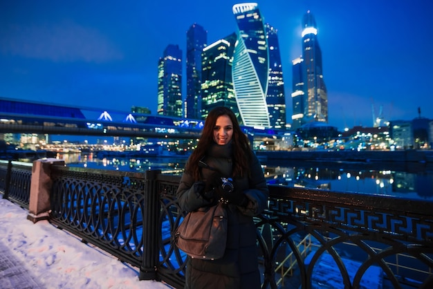 Beautiful young girl stands on the background of moscow city in winter