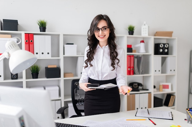 A beautiful young girl stands near an office desk and holds a pen, notebook and calculator in her hands. the girl is leading a besside.