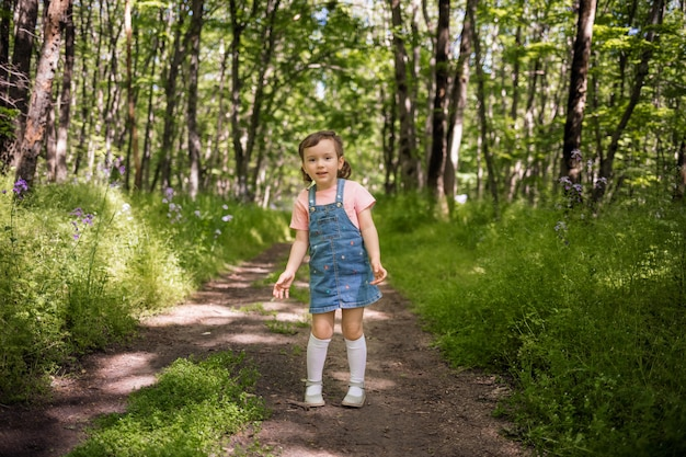A beautiful young girl stands on a path in the woods in a denim sundress and looks at the camera. summer walks in the forest.