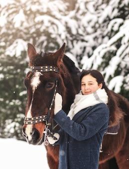 美しい少女は自然の中で冬に茶色の馬を撫でる