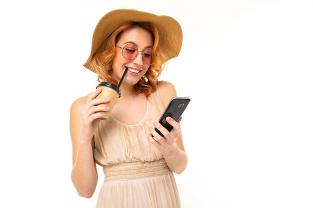 Beautiful young girl in a summer image with a phone and a glass of cocktail on a white background