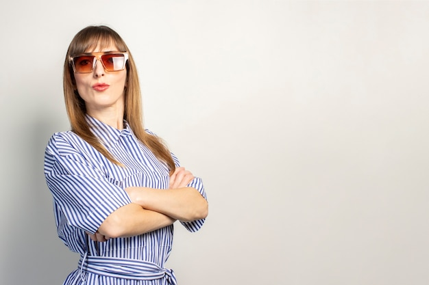 Beautiful young girl in sunglasses on a light background