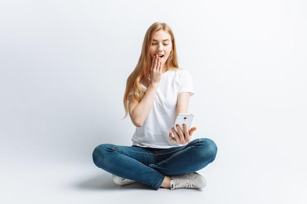 電話で話している美しい若い女の子、驚きやニュースや割引からの女の子にショック、陽気で前向きな