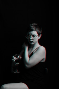 Beautiful young girl tries and evaluates red wine. black and white with glitch effect
